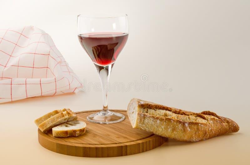 Vite rossa in un vetro con pane su un piatto di legno immagine stock