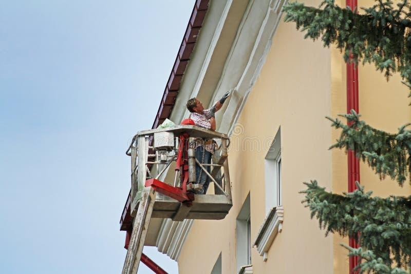 Vitebsk, Belarus - August 05, 2013: Woman in bucket at height painting facade of building in Vitebsk stock images