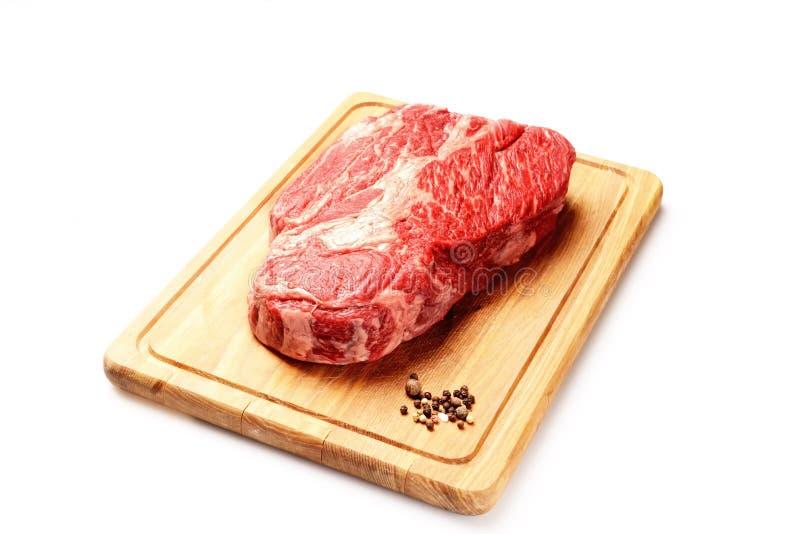 Vitello di marmo con le spezie su un tagliere, un coltello per carne su un fondo bianco fotografia stock libera da diritti