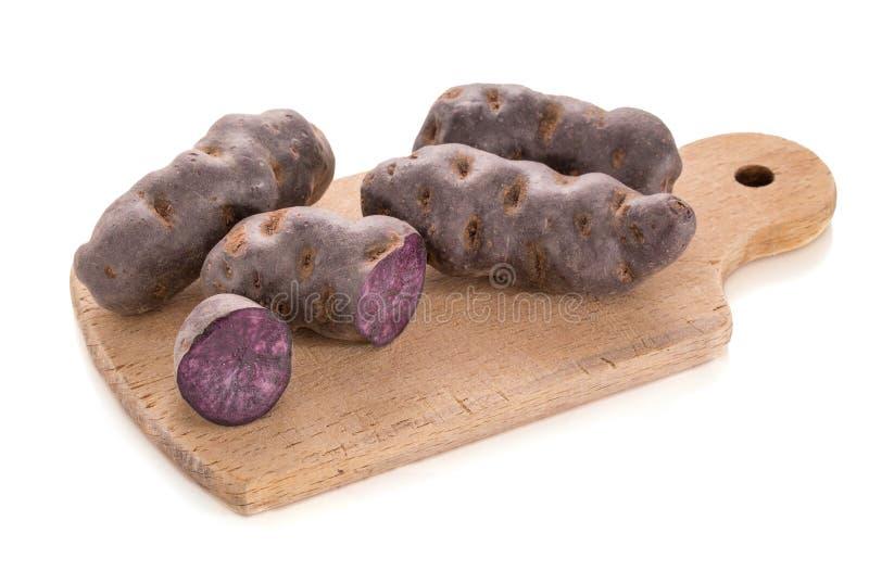 Vitelotte, purpere aardappel in stapels op een houten scherpe raad stock fotografie