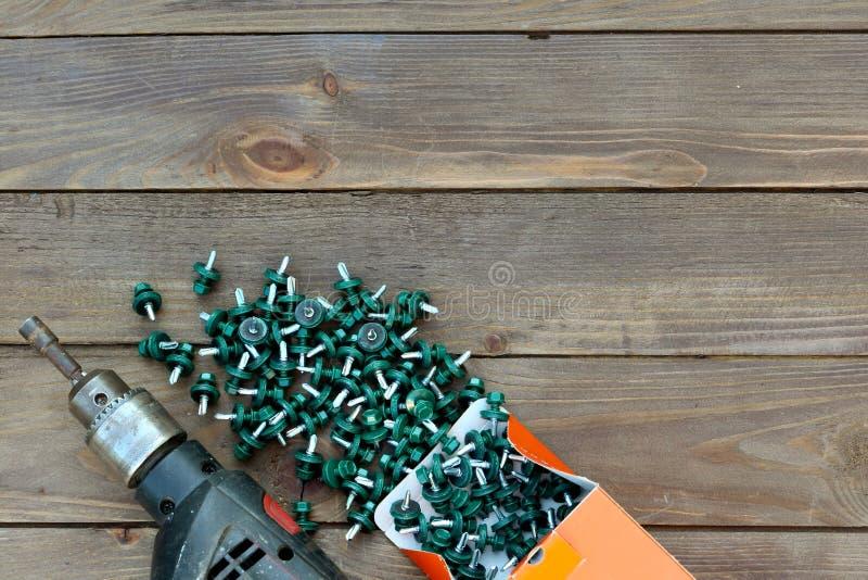Viti del tetto e un trapano su una tavola di legno La vista dalla parte superiore Modello per la festa del lavoro Roofer, coprent immagine stock libera da diritti