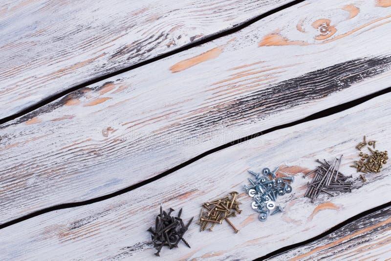Viti nere, d'argento e dorate su fondo di legno fotografia stock libera da diritti