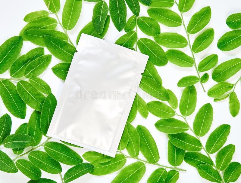 Vitkrämpåsen på den tomma etikettpacken för åtlöje upp på en gräsplan lämnar bakgrund Begreppet av naturliga skönhetsprodukter royaltyfria bilder
