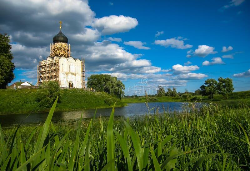 Vitkyrka med blåa kupoler och sceniska moln, Bogolubovo, Ryssland arkivbilder
