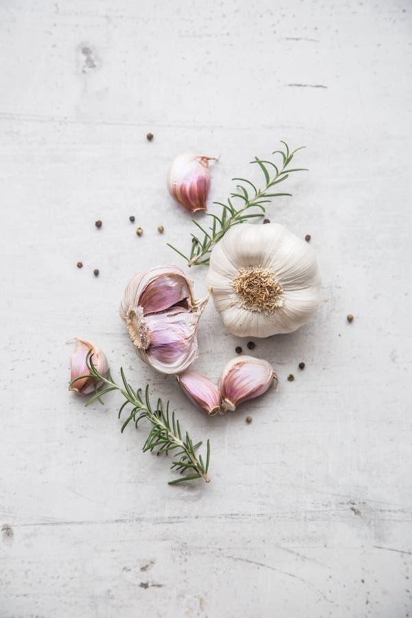 Vitlök heads ny vitlök för kulor tre Ny vitlök med rosmarin och peppar på vitbetong stiger ombord royaltyfria bilder
