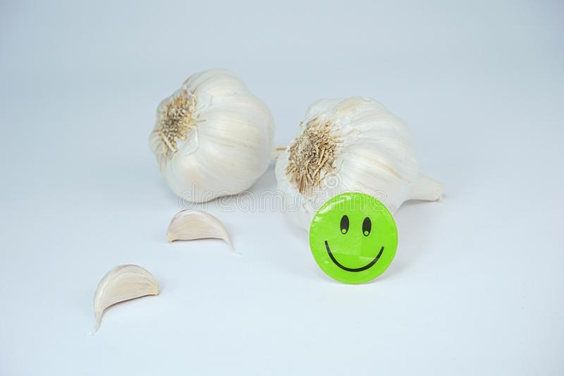 Vitlök och lycklig grön smiley framsida som isoleras på vit bakgrund royaltyfria bilder