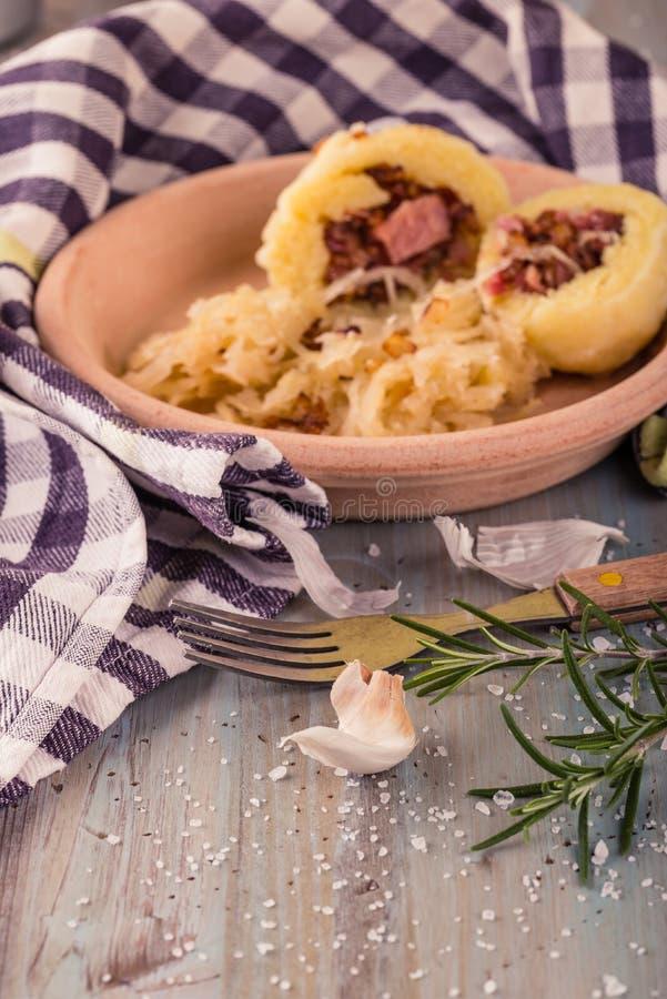 Vitlök och rosmarin av klimpar fyllde framme vid rökt grisköttkött med kål royaltyfri bild
