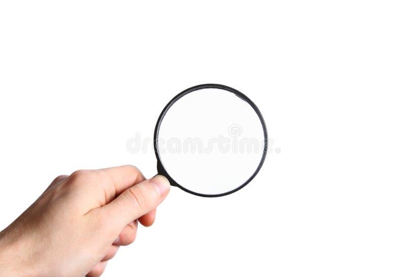 Räcka innehav ett svart förstoringsglas som isoleras på vitbakgrund arkivbild