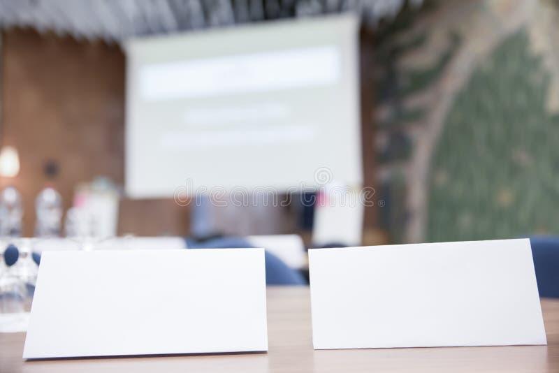 Vitnamnetiketter på kontorsskrivbordet på det offentliga mötet royaltyfria bilder