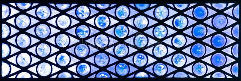 Vitrail avec des cercles et des triangles dans les teintes bleues photo libre de droits