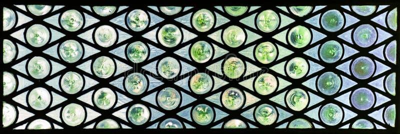 Vitrail avec des cercles et des triangles dans les teintes vertes et bleues images stock