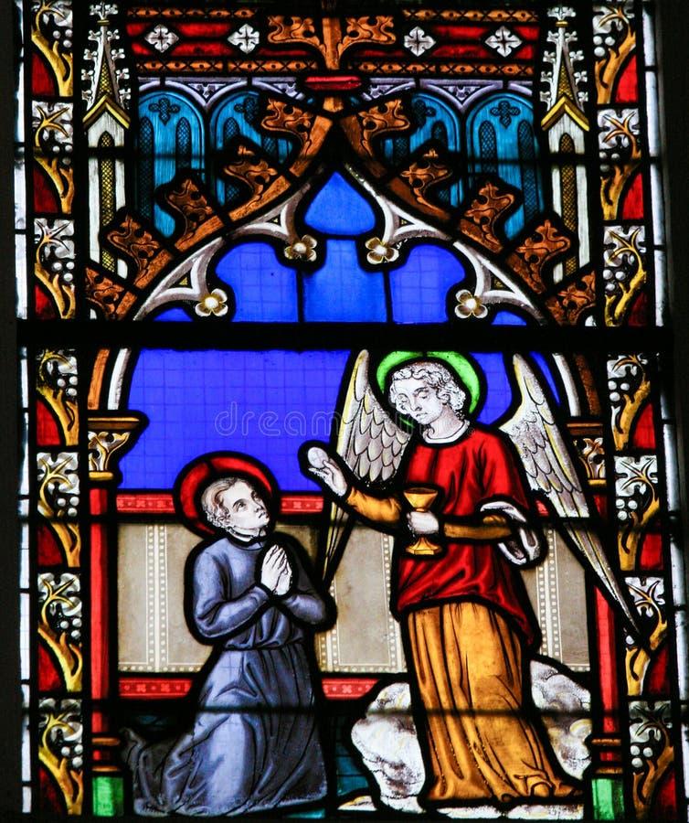 Vitral - anjo que dá o comunhão santamente fotografia de stock