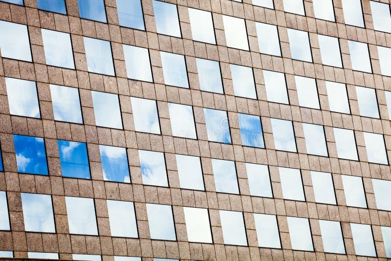 Vitraux de façade avec le ciel reflété Immeuble de bureaux moderne image libre de droits