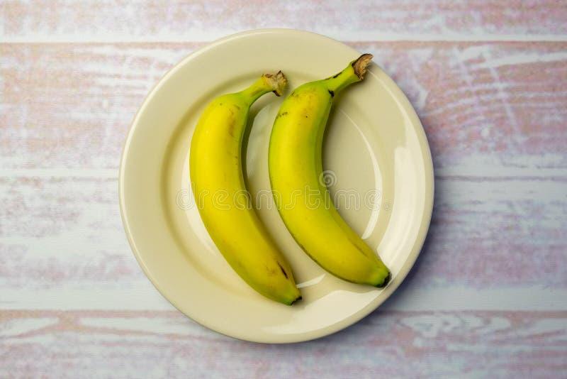 Vitrundaplatta med två bananer arkivbilder