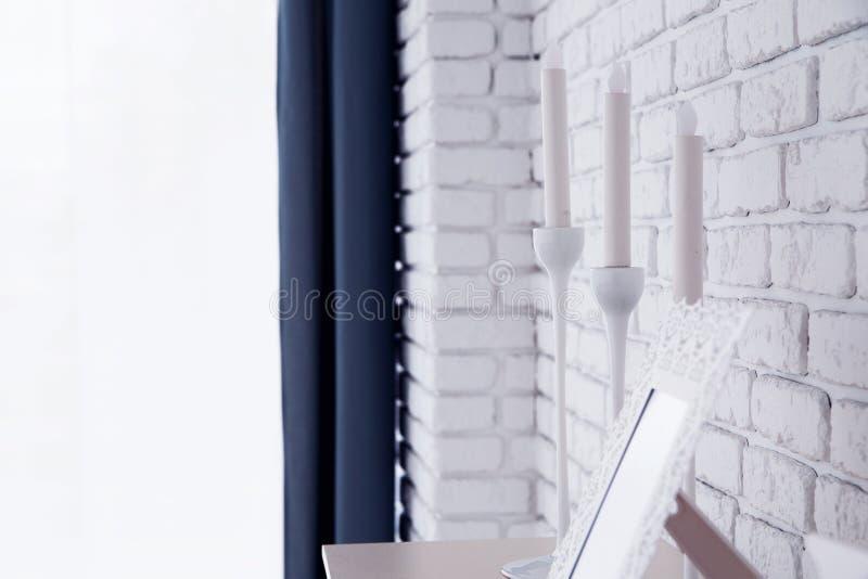 Vitstearinljus på en hylla över tegelstenväggen royaltyfri bild