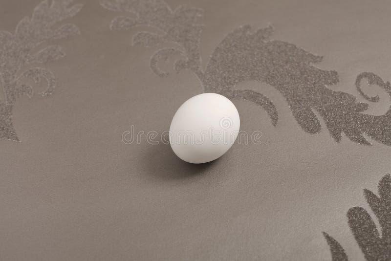 Vitt ägg på pastellfärgad bakgrund royaltyfri bild