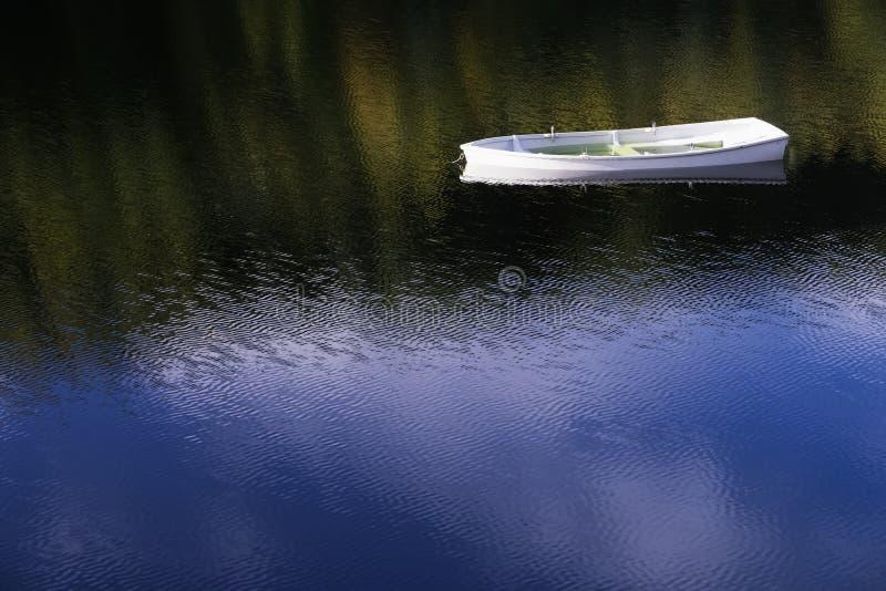 Vitt änglalikt enkelt ensamt fartyg som svävar fridsam salighetmindfulness i lugna vatten med reflexionssolen för blå himmel som  royaltyfria bilder