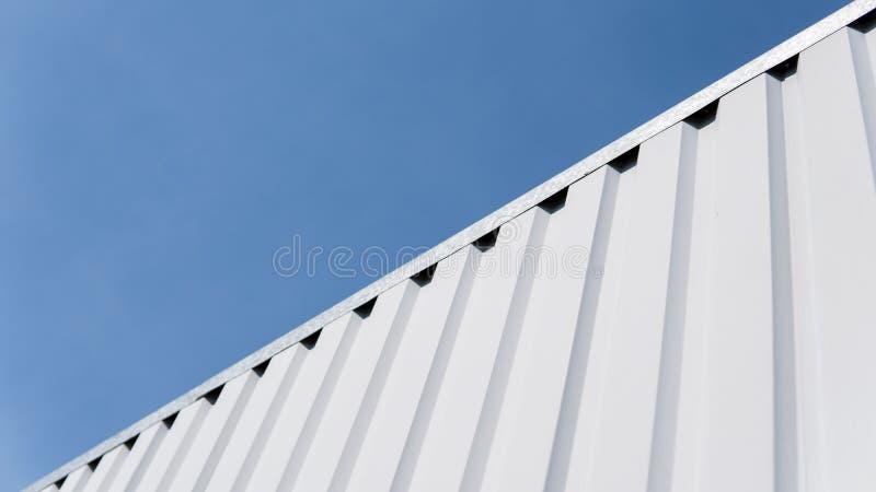 Vitt ark för metall för industribyggnad och konstruktion på bakgrund för blå himmel Takarkmetall eller korrugerade tak royaltyfri fotografi
