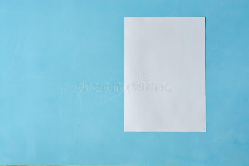 Vitt arkpapper isoleted på det ljust - blå bakgrund royaltyfria foton