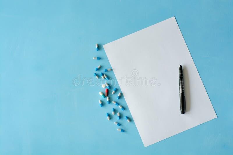 Vitt arkpapper med den svarta pennan och kulöra olika piller royaltyfria foton