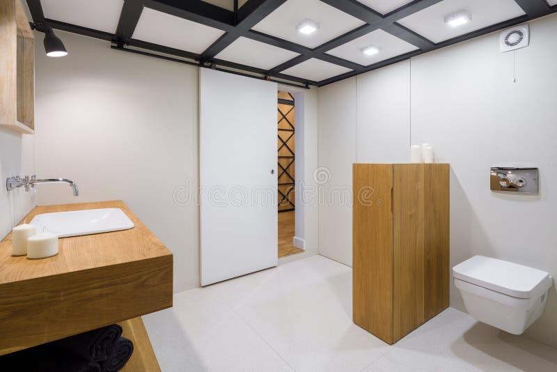 Vitt badrum med trämöblemang royaltyfria bilder
