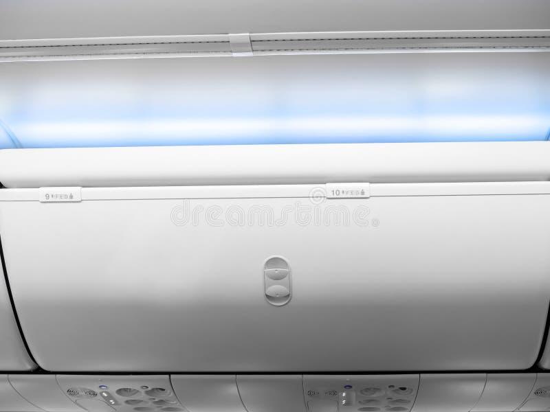 Vitt bagageskåp nummer 9 och 10 med blått ljus i kabinekonomiklassen i kommersiellt flygplan arkivfoton