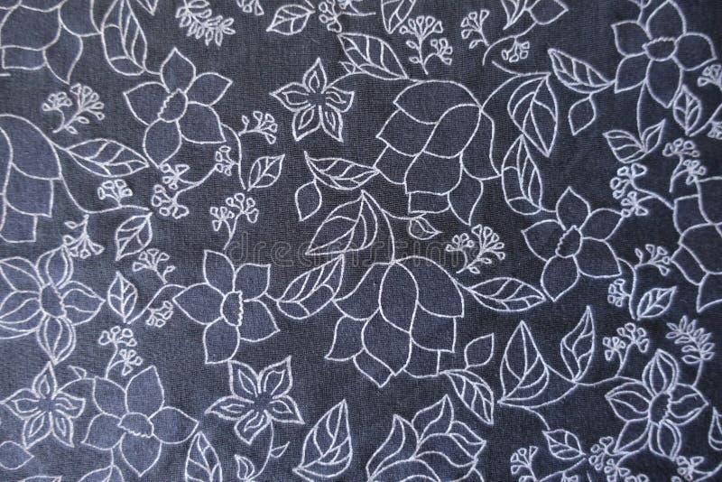 Vitt blom- tryck på mörker - blått tyg från över arkivbilder