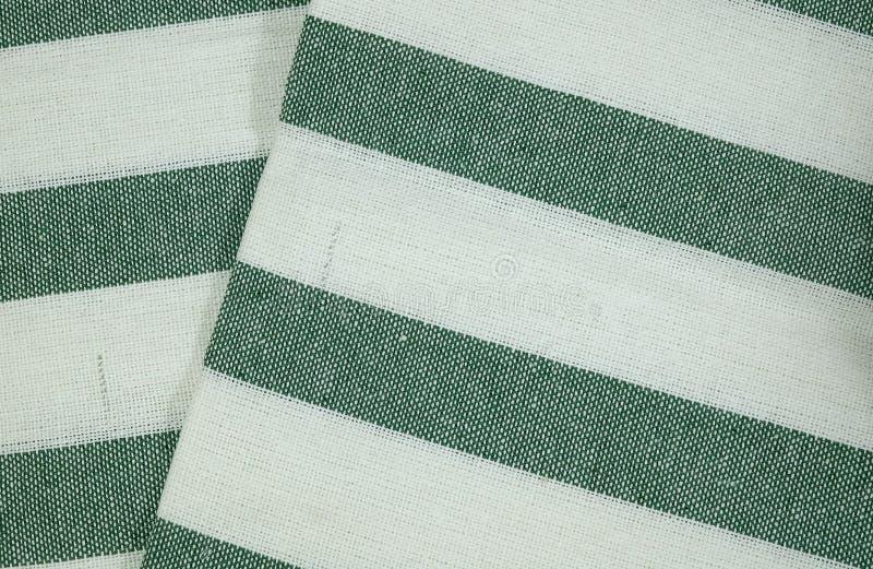 Vitt bomullstyg med gröna band mönstrar bakgrund royaltyfria foton