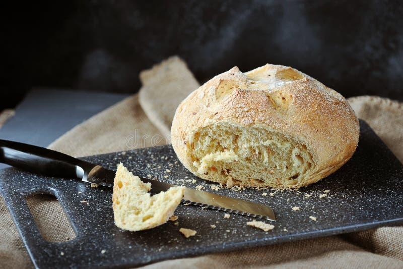 Vitt bröd, klippt stycke av bröd, brödsmulor och brödkniven royaltyfri bild