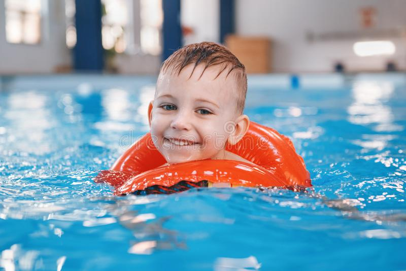 Vitt Caucasian barn i simbassäng Förskole- pojkeutbildning som svävar med den röda cirkelcirkeln i vatten arkivfoto