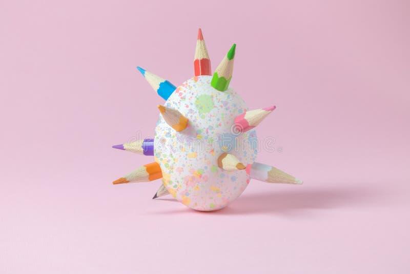 Vitt easter ägg med mångfärgade träfärgpennaspjut och som färgar med vattenfärgfärgstänk royaltyfria bilder