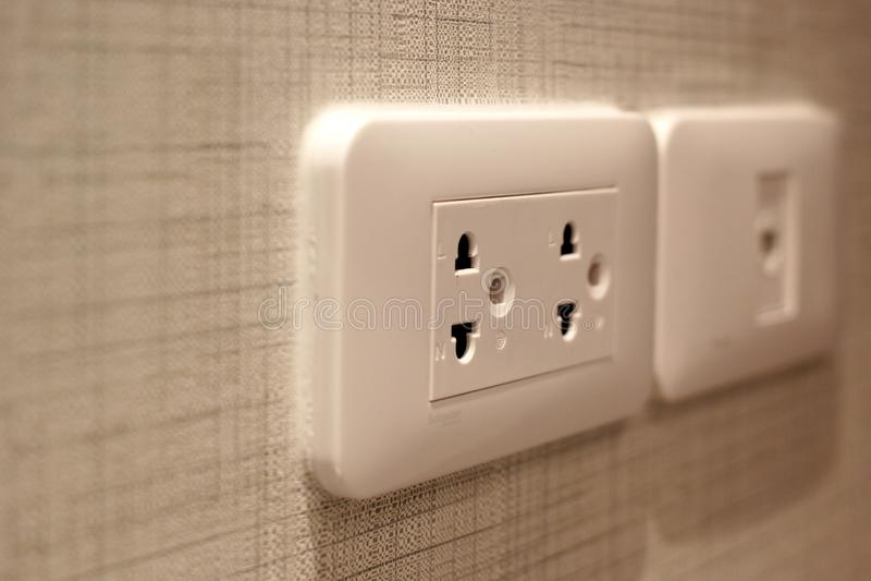 Vitt elektriskt uttag på väggen royaltyfri foto