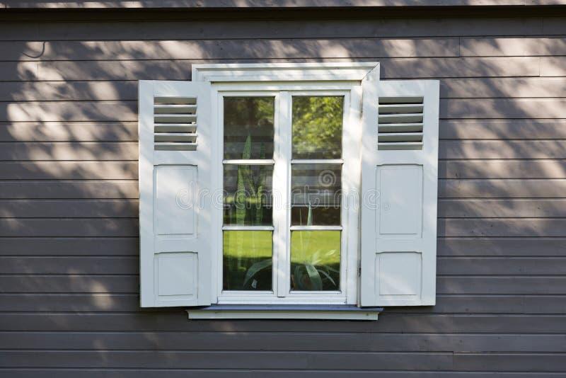 Vitt fönster för liten tappning med slutare på den trägråa väggen fotografering för bildbyråer