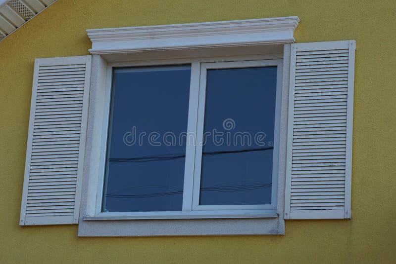 Vitt fönster med öppna träslutare på den gula väggen av byggnaden royaltyfri foto