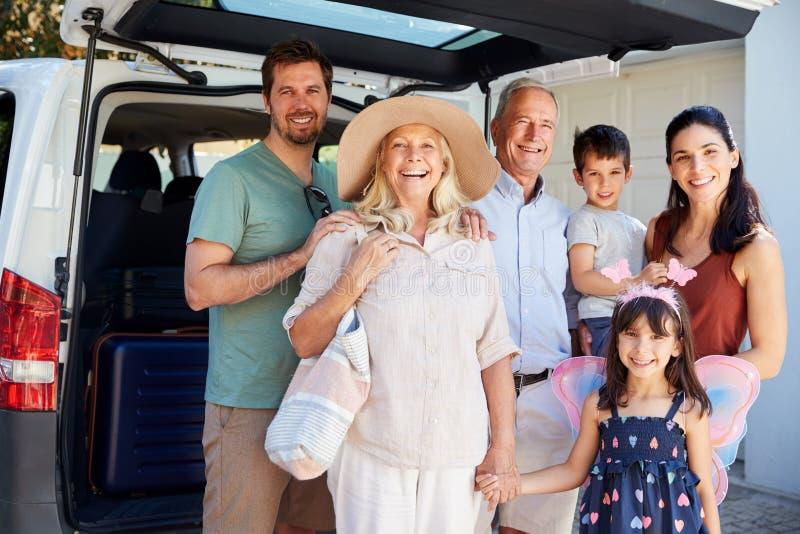 Vitt familjanseende för tre utveckling av bilen som ler till kameran, innan att lämna för semester royaltyfri foto