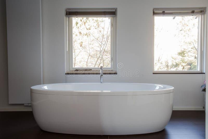 Vitt fristående badkar i planlagt modernt badrum arkivfoto