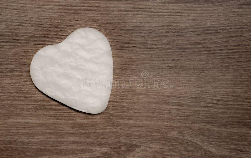 Vitt hjärtaformpapper cutted för gåva för överraskningvalentindag på brun träbakgrund, foto för bästa sikt arkivfoton