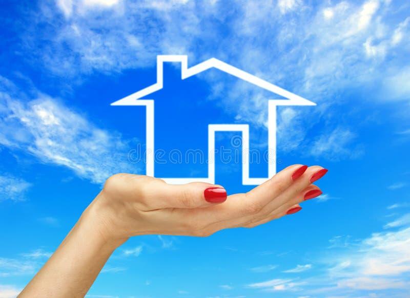 Vitt hus i kvinnahand över blå himmel för delshus för gods försäljning för hyra verklig arkivbild