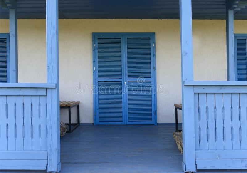 Vitt hus med ljus - blå dörr, fönster och terrass royaltyfria foton