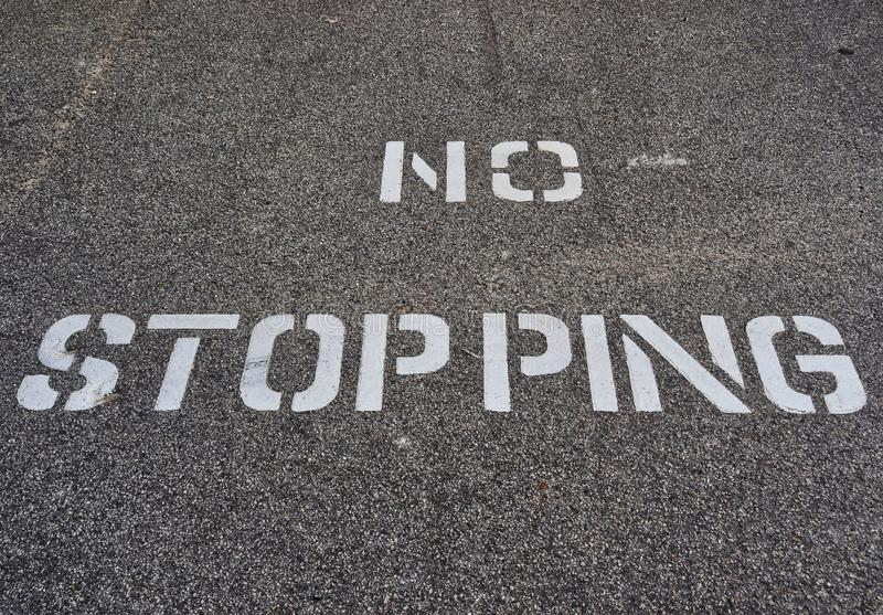 Vitt inget stoppande tecken som stencileras på den svarta vägen royaltyfri foto