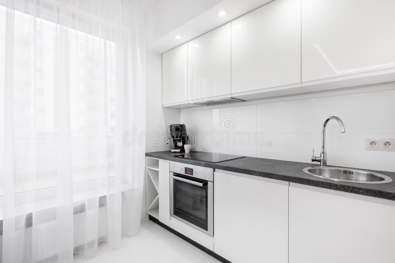 Vitt kök med den svarta countertopen arkivfoton