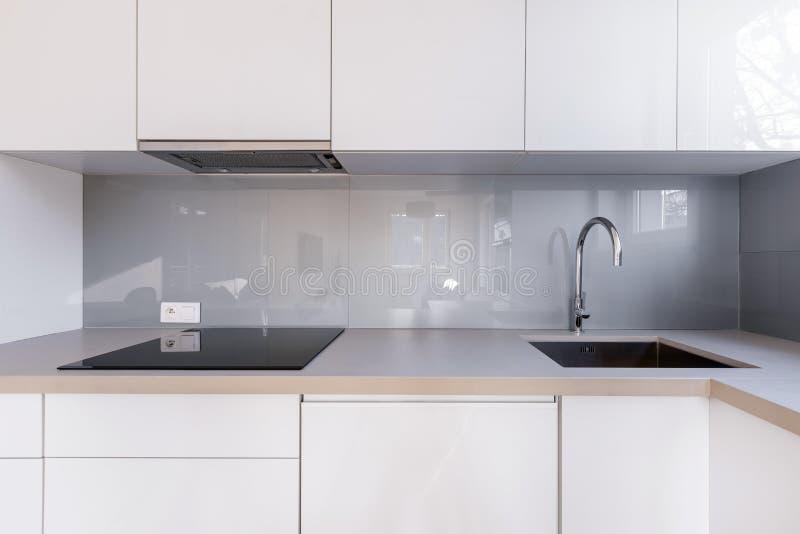 Vitt kök med grå backsplash royaltyfria foton