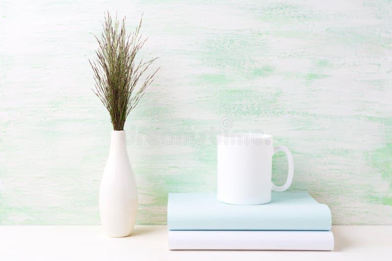 Vitt kaffe rånar modellen med mörkt änggräs i vas och böcker royaltyfri bild