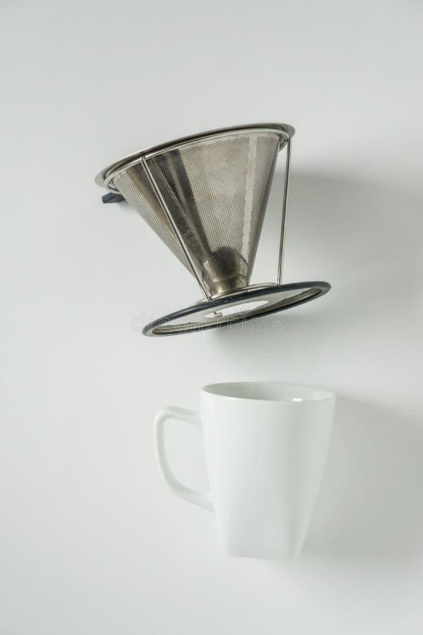 Vitt kaffe rånar på vit bakgrund med filterless metall häller över droppandekotte royaltyfri bild