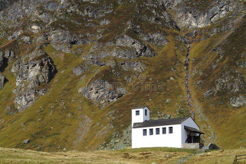 Vitt kapell i alpint landskap royaltyfria bilder