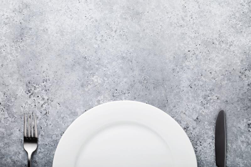 Vitt keramiskt platta och bestick på tabellen med många bakgrundsklimpmat meat mycket royaltyfri foto