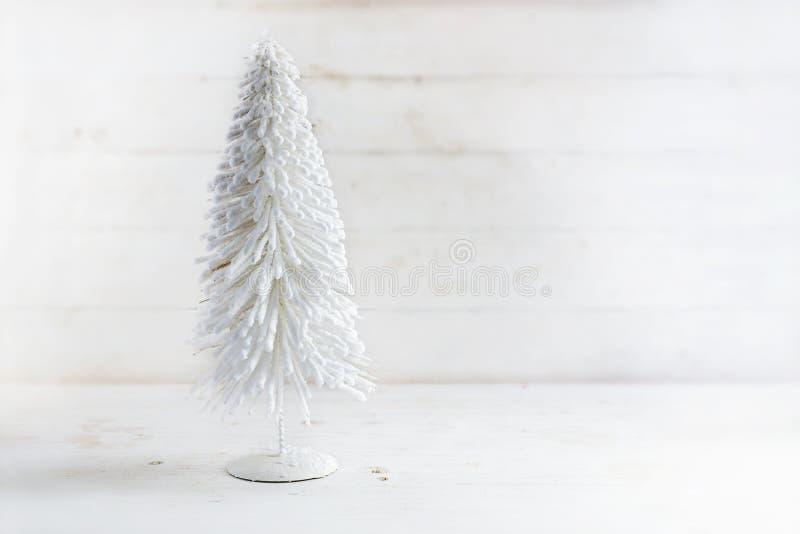 Vitt konstgjort julträd från flockas tråd på en lantlig wh royaltyfri foto