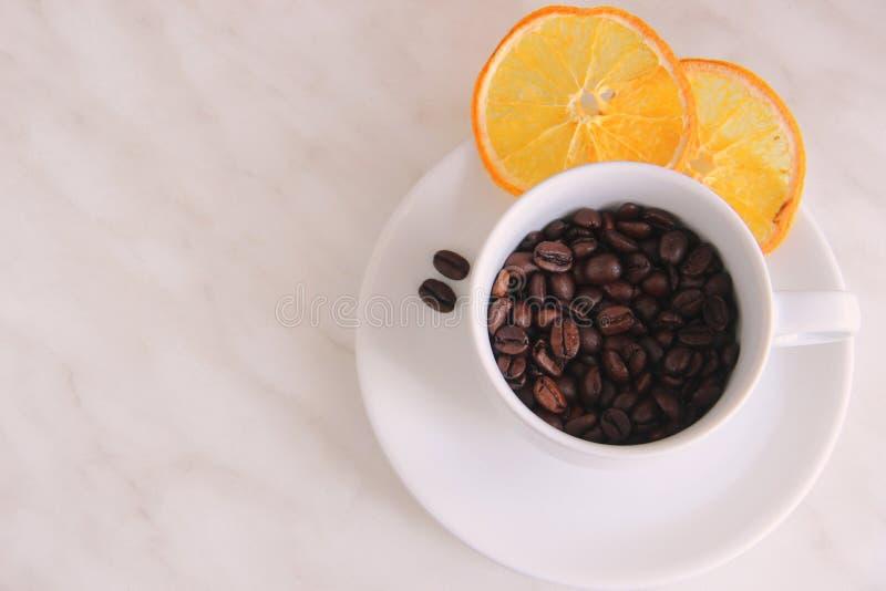 Vitt kopp och tefat, kaffebönor, skivor av den torkade apelsinen på en grå tabell, bästa sikt arkivbilder