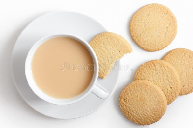 Vitt kopp te och tefat med mördegskakakex från över royaltyfri foto
