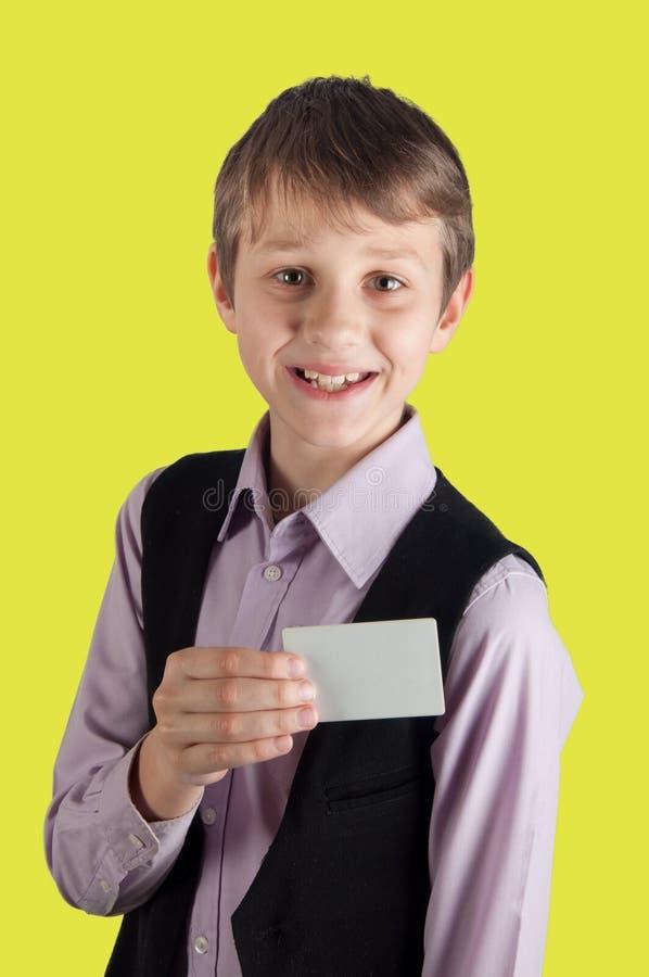 Vitt kort för gladlynt pojkevisning på gul bakgrund royaltyfria foton